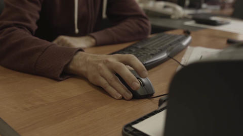 Man's hand moves computer mouse focus in on a wooden table Footage