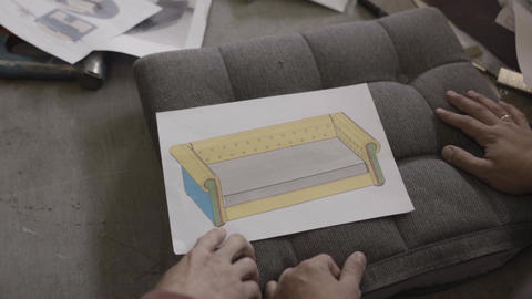 Two men look at drawing sofa and discuss it in furniture factory Footage