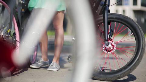 Wheels of three bicycles focus in, girl moves one of a bicycle in summer day Footage
