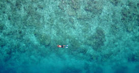 v06455 Aerial flying drone view of Maldives white sandy beach young people snork Footage