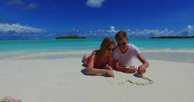 v07272 Maldives white sandy beach 2 people young couple man woman drawing love h Footage
