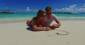 v07273 Maldives white sandy beach 2 people young couple man woman drawing love h Footage
