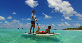 v07275 Maldives white sandy beach 2 people young couple man woman paddleboard ro Filmmaterial
