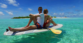 v07296 Maldives white sandy beach 2 people young couple man woman paddleboard ro ビデオ