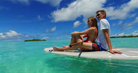v07308 Maldives white sandy beach 2 people young couple man woman paddleboard ro Footage