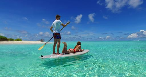 v07315 Maldives white sandy beach 2 people young couple man woman paddleboard ro Foto