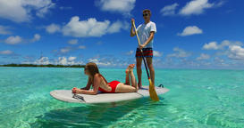 v07370 Maldives white sandy beach 2 people young couple man woman paddleboard ro Filmmaterial