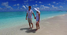 v07491 Maldives white sandy beach 2 people a young couple man woman walking toge Filmmaterial