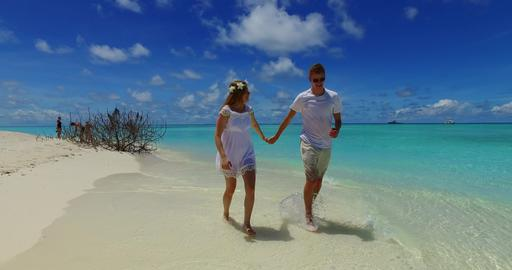 v07532 Maldives white sandy beach 2 people a young couple man woman walking toge Foto