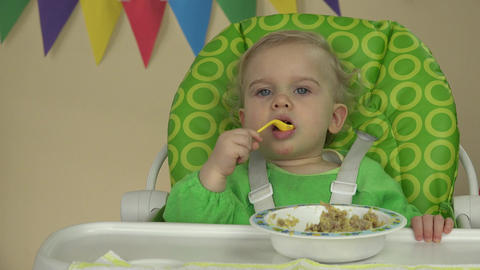 baby child sitting in chair with a spoon and eating delicious child food Live Action