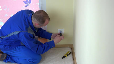 Worker man repair an electrical outlet in apartment Footage