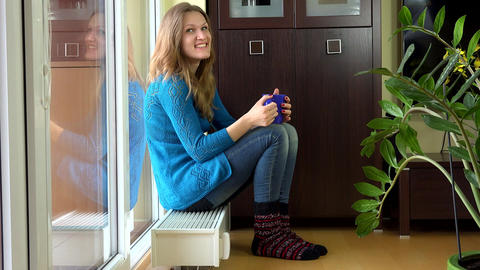 Happy woman with warm clothes drink tea and dream sitting on warm radiator Footage