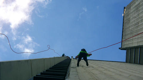 Fearless people descend down with safety rope on skyscraper high building wall Live Action