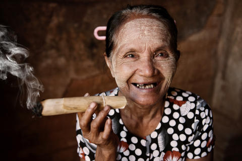 Happy old wrinkled Asian woman smoking Photo