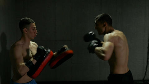 Slow motion of two male fighters training in gym studio with boxing gloves and t Footage