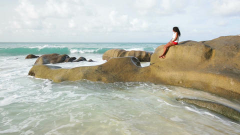 Woman Sitting On Rock By The Beach In Mahe, Seychelles Footage