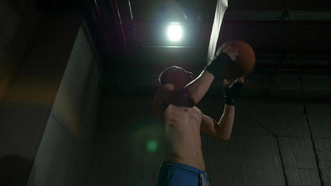 Athletic focused boxer training hitting ball inside sportive studio wearing hand Live Action