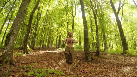 A thin man stands in a sunny dense forest and folds his hands in a gesture namas Footage