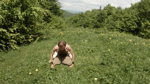 Man doing a bridge, yoga in green grass in a mountain forest Live Action