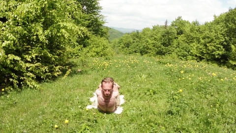 man lies on his stomach, his head is raised, in the green grass in the mountain  Live Action