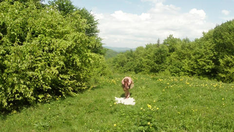 Yogi doing physical exercise in yellow flowers in the forest on green grass in t Footage