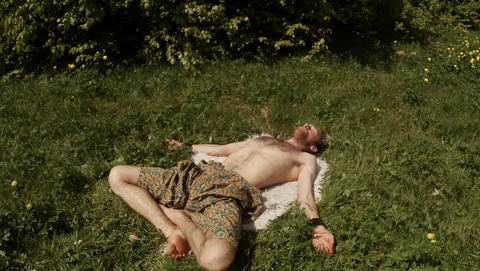 Man lying on the skin in a relaxing asana, yoga in the forest on the green grass Footage