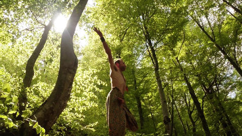 Man is engaged in yoga under the sun on a mossy stone in a dense green forest Footage