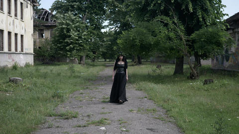 Young macabre woman with gothic black clothes and crown of ivy leaves walking am Live Action