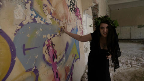 Mad young girl dressed as a witch with evil sneer scratching wall of ruined mans Live Action