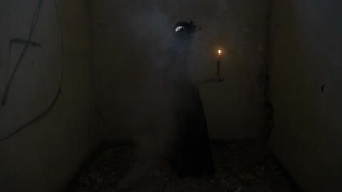 Gothic dressed vampire woman holding a candle turning around in a smoky abandone Footage
