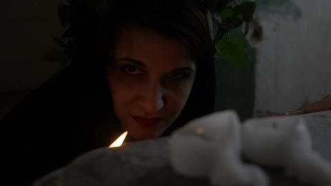 Closeup of gothic woman possessed by a demon snarling and hissing behind candles Footage