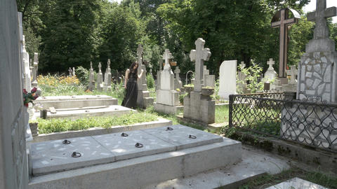 Funeral gothic girl walking beside tombstones in ancient graveyard contemplating Live Action