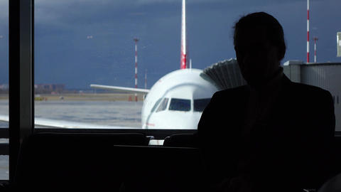 Man work on laptop in airport lounge, silhouetted view against airliner Footage