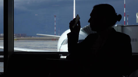 Man pick up phone and have short conversation, silhouetted view Footage
