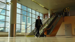 Man walk downstairs on escalator and come away, airport terminal passage Footage
