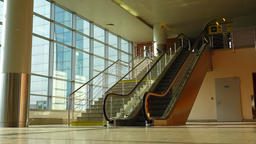 Escalator travelling down beside stairway, empty passage at airport Footage