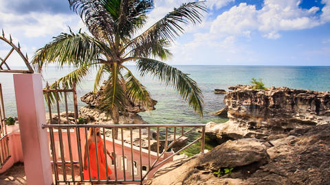 Girl in Red Goes Downstairs Hand-rail Leads to Sea Stones Palm Footage