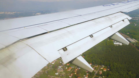 Airplane wing during landing with flaps down on the sky over land Footage