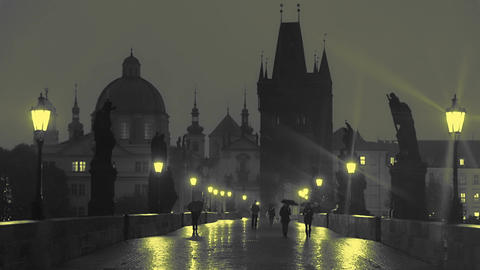 Pedestrians with Umbrellas on the Charles Bridge at Night. Slow Motion Footage