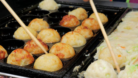 Cooking 'Takoyaki' a ball-shaped dumpling fried snack. Japanese Street food Footage