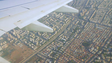 Airplane wing on the sky and over land with building of Tel Aviv city Footage