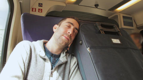 Young man traveling on a train and sleep on blue suitcase next to him Footage