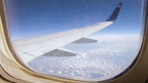 Frozen condensation of ice crystals on the window of an airplane with the wing i Footage