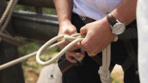 Extreme professional climber who wears a suit prepares his safety ropes for a bi Footage