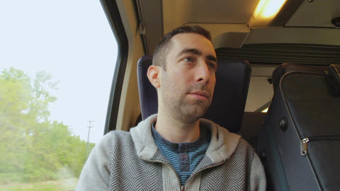 Young man traveling on a train and talking with someone Footage