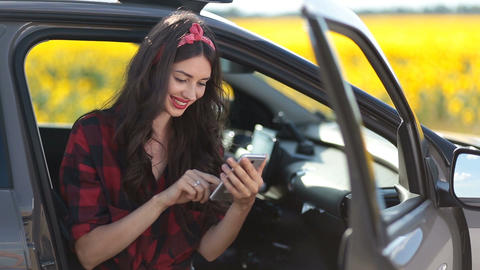 Cute girl browsing the net with smartphone in car Live Action