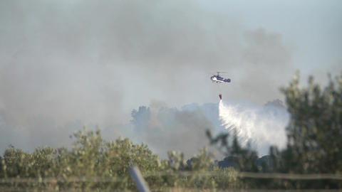 Helicopter pouring water for fire extinguishing Archivo