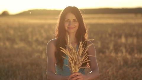 Lovely girl holding ripened wheat ears on field Image