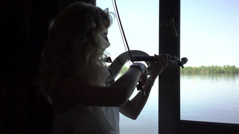 4K Silhouette Of A Girl Playing The Violin Footage
