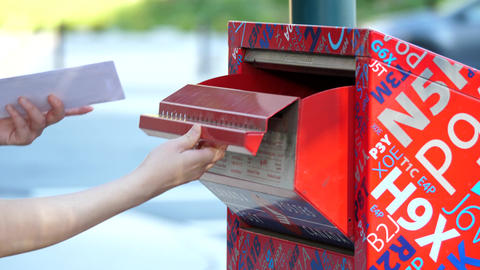 Motion of woman placing mail in a canadian mail box with blur traffic flow backg Footage